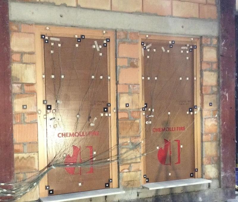 X240 - EI 45 1A Forata sp. 70 - Porta Chemolli Fire Systems, famiglia X240, ad un'anta in legno con telaio in legno, funzionamento a battente, classificata resistente al fuoco EI1 45 REI 45 secondo la norma EN 13501-2:2007 + A1:2009.     La famiglia di porte, nelle varie versioni, ha superato le prove di cui ai certificati di prova:  Rapporto di classificazione 15-000198-PR03 rilasciato in data 03/06/2015, rapporto di prova 15-000198-PR01 rilasciato in data 18/08/2015 dal laboratorio IFT Rosenheim MBH, omologazione TN268EI1045P004 del 29/10/15.     Porta a filo muro, con anta da 62 mm di spessore, con movimento rotatorio su asse verticale, tamburata con isolante interno a griglie, struttura e battute in massiccio, rivestita con due piastre d'acciaio preforate da 1 mm di spessore. La struttura interna è realizzata con un perimetro in legno massiccio e da traversi sempre in legno massiccio.     Montaggio consentito su pareti in muratura o cartongesso di spessore minimo pari a 110 mm, con resistenza al fuoco EI 45 – REI 45. Falsotelaio in legno da inserirsi sulla parete in muratura, sezione da 25 mm (minimo) x spessore muro, oppure rinforzi in abete da collocarsi fra i montanti della parete in cartongesso, a cura del cliente o fissaggio diretto al supporto. Rostri di tenuta in caso di incendio Chemolli Firebolt A1, A2, cerniere a scomparsa. Serratura dotata di cilindro. Guarnizioni intumescenti installate sul telaio e sui bordi dell'anta.
